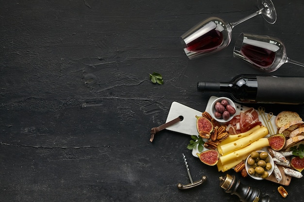 Two glasses of red wine and cheese plate with fruit on the black stone