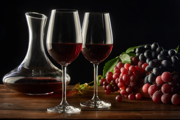 Two glasses of red wine decanter and different types of grapes on a wooden table black background