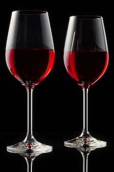 Two glasses of red wine on a glossy table. black background.