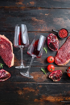 Two glasses of red wine near raw beef steaks with seasonings over rustic dark wood background, top view.