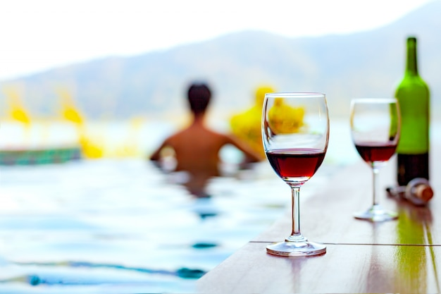 Two glasses of red wine near the swimming pool with a man is swimming in the pool