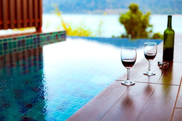 Two glasses of red wine near the swimming pool with a spectacular view of the sea