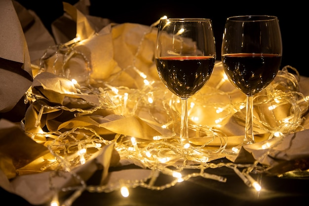 Two glasses of red wine stand in a shining garland