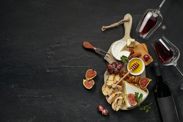 Two glasses of red wine and a tasty cheese plate with fruit, grape, nuts and toasted bread on a wooden kitchen plate on the black stone background