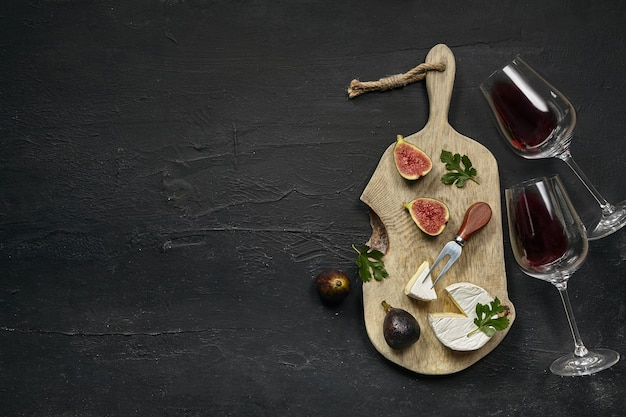 Two glasses of red wine and a tasty cheese plate with fruit on a wooden kitchen plate on the black stone
