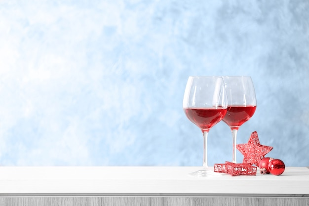 Two glasses of red wine with christmas accessories on grey wall background