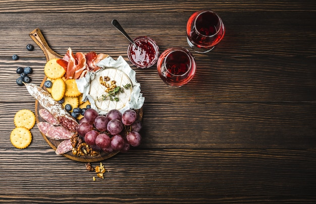 Two glasses of red wine, wooden board, cold meat, cheese, fruit, dip. wooden background