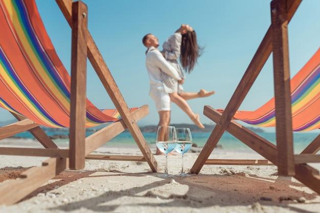 抱きしめるカップルビーチを反映して2つのメガネ。ハネムーン。グラスワインの美しい反射。夏休み。熱帯の休暇