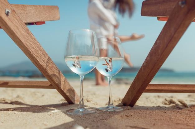 ビーチで抱きしめるカップルを反映した2つのメガネ。ハネムーン。ワインのグラスに美しい反射。夏休み。熱帯の休暇