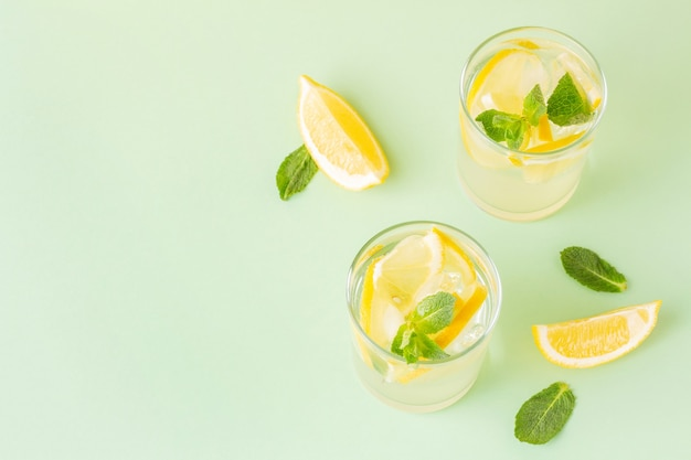 Two glasses of refreshing summer drinks with lemon and mint leaves on a mint background