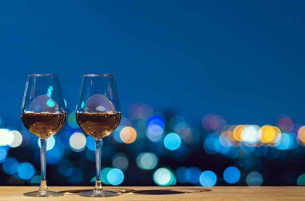 Two glasses of rose wine with bokeh city colorful light from rooftop building.