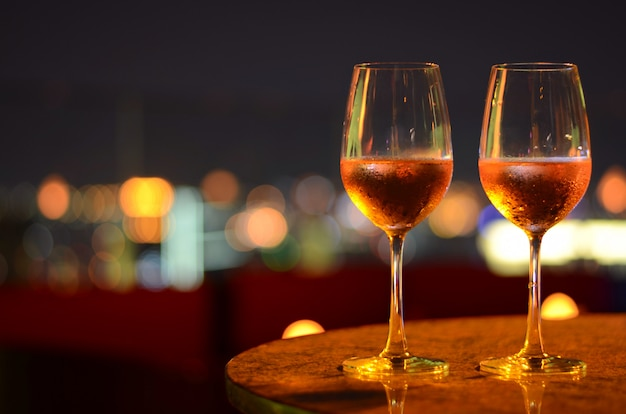 Two glasses of rose wine with bokeh light at bangkok city and colorful light from rooftop