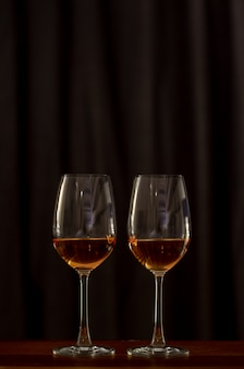 Two glasses of rose wine on wooden table to celebrate for a couple.