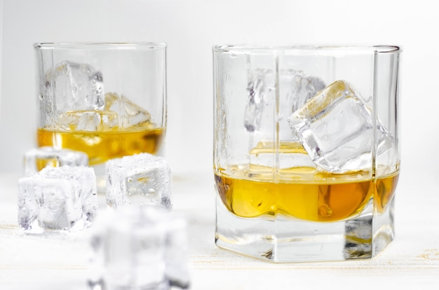 Two glasses of scotch whiskey with ice cubes on white