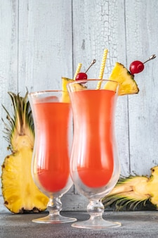 Two glasses of singapore sling on wooden wall