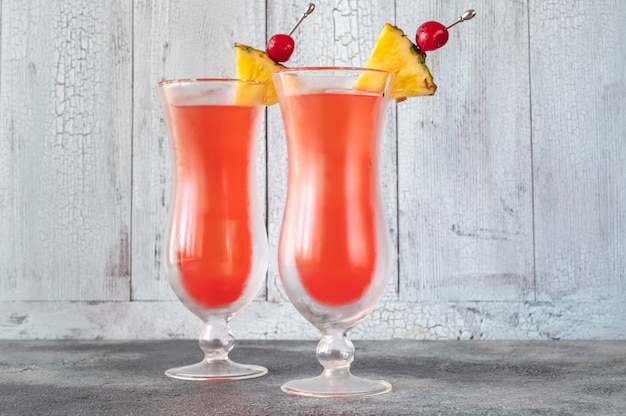Two glasses of singapore sling on wooden