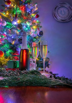 Two glasses of sparkling champagne at new year eve night with clock showing two minutes before midnight. christmas decoration .