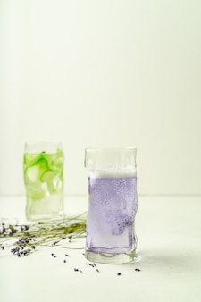 Two glasses of summer refreshing drinks, lavender lemonade and cucumber infused water
