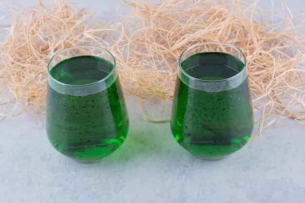 Due bicchieri di succo di dragoncello su sfondo marmo. foto di alta qualità