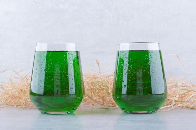 Due bicchieri di succo di dragoncello su marmo