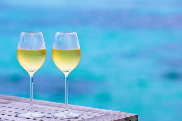 Two glasses of tasty white wine the sea