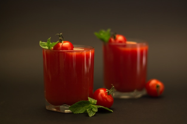 Two glasses of tomato juice with cherry tomatoes and mint with a black background