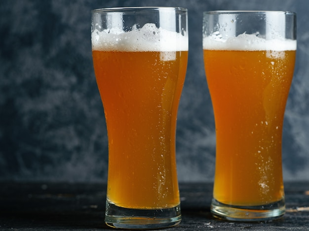 Two glasses of unfiltered cold beer on the table close-up