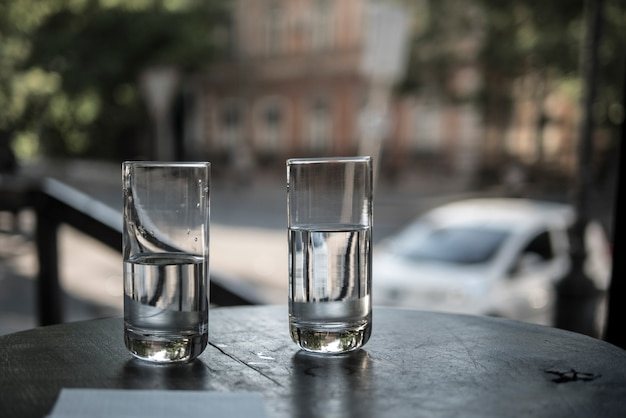 Two glasses of water stand on a table in a restaurant on the background of city streets