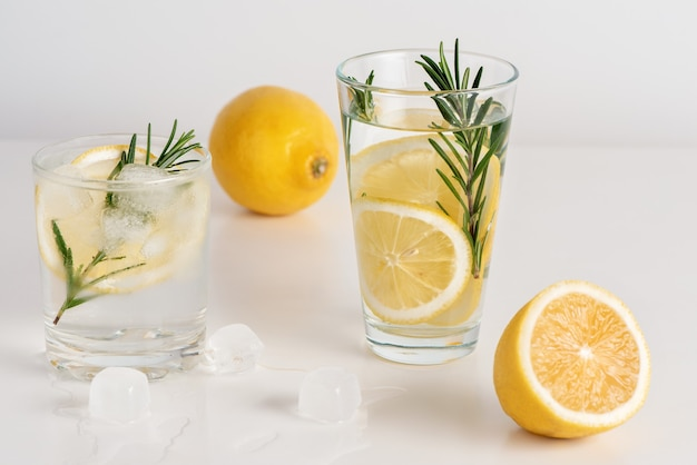 Two glasses of water with lemon slices, rosemary and ice.