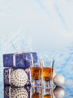 Two glasses of whiskey or bourbon with christmas decoration on a light bokeh background. new year, christmas and winter holidays whiskey mood concept