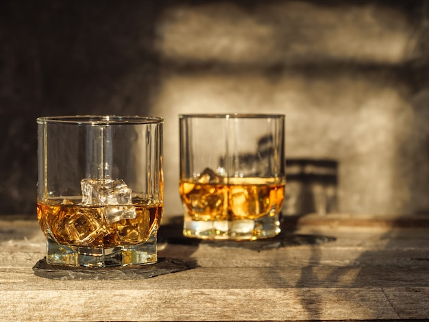 Two glasses of whiskey stand on an old wooden table. horizontal photo. copy space.