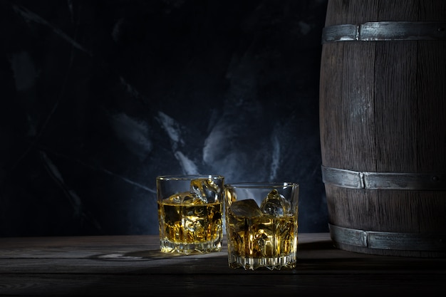 Two glasses of whiskey with ice and wooden barrel