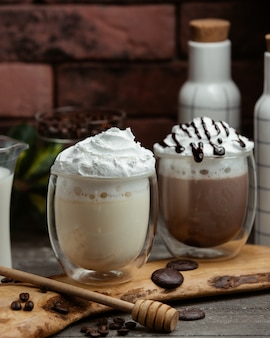 Two glasses of white chocolate mocha and chocolate mocha with whipped cream