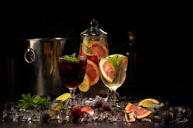 Two glasses of white and red wine sangria with blackberries, strawberries, grapefruit, lime and orange slices with ice and mint
