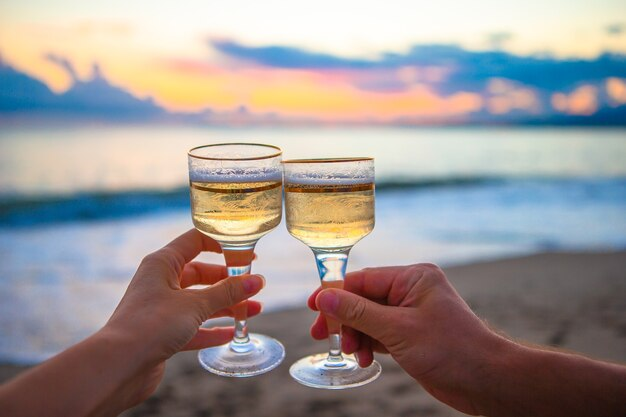 Two glasses on the white sandy beach