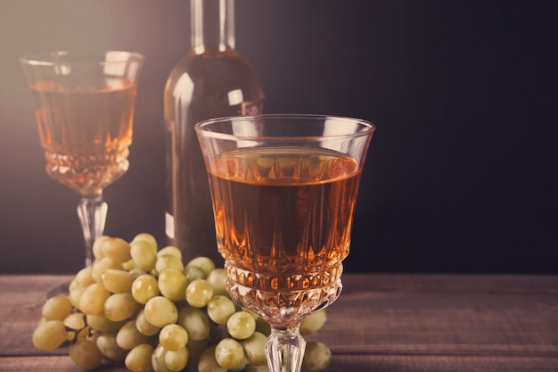 Two glasses of white wine, bottle and bunch of grapes standing on a wooden table