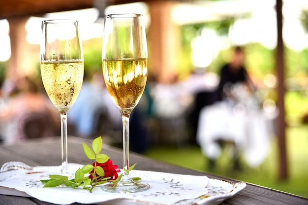 Two glasses of white wine ready for a wedding couple to toast.