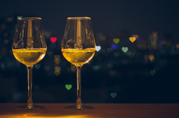 Two glasses of white wine on wooden table of rooftop bar