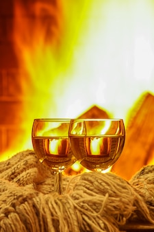 Two glasses of white wine  and wool things near cozy fireplace, vertical.