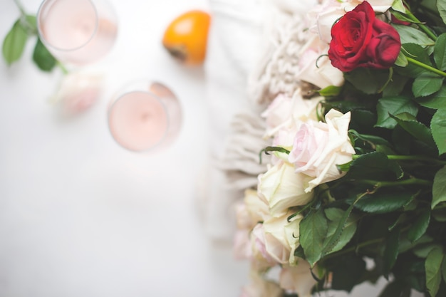 Two glasses of wine and a large bouquet of roses at the house near the window. free space for text.