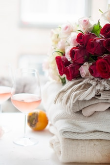 Two glasses of wine and a lot of winter warm clothes at home near the window. cat, large bouquet of roses and autumn fruit in frame. the city is outside the window. free space for text.