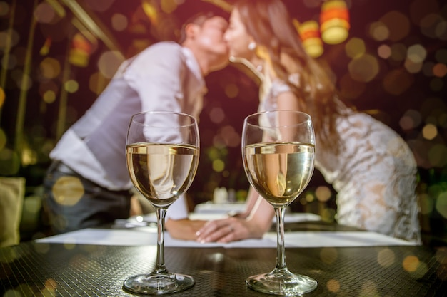Two glasses of wine place on table. there are asian couple kissing together on blured background.