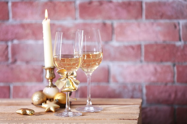 Two glasses of wine with candle and christmas toys on brick wall