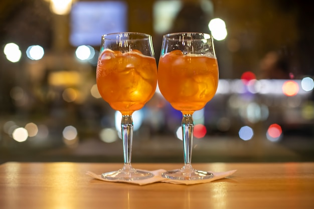 Two glasses of wine with orange coctail stand on a wooden table in a cafeitalian alcoholic drink