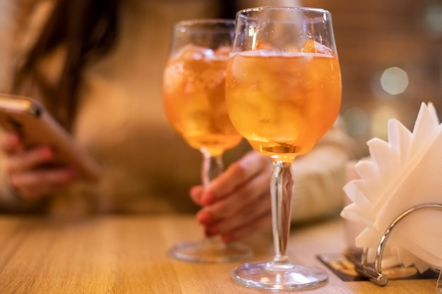 Two glasses of wine with spritz coctail stand on a wooden table in a cafe, in the rays of the setting sun. italian alcoholic drink with oranges and ice. close-up, selective focus