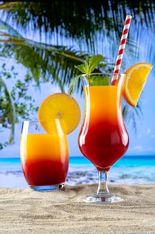 Два бокала с напитком, секс на пляже на песке и пляжный рай на заднем плане