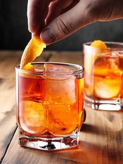 木製のテーブルの上にネグローニカクテルとグラス2杯。縦の写真。