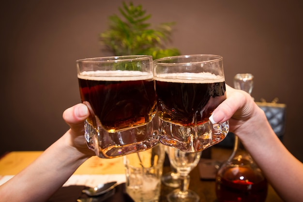 Two glasses with alcohol in hands.