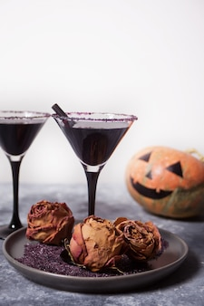 Two glasses with black cocktail, dried roses, jack-o'-lantern for halloween party on the dark background