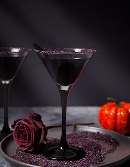 Two glasses with black cocktail, dried roses, pumpkin for halloween party on the dark background